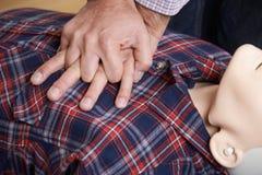 Mann, der CPR-Technik auf Attrappe in der Klasse der ersten Hilfe verwendet Lizenzfreie Stockfotos