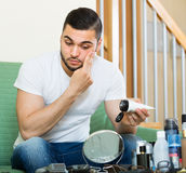 Mann, der Creme auf Gesichtshaut aufträgt Stockbilder