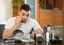 Mann, der Creme auf Gesichtshaut aufträgt Lizenzfreies Stockfoto