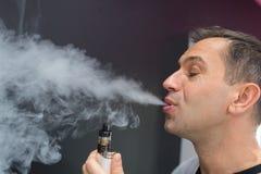 Mann, der Dampf von der elektronischen Zigarette ausatmet Stockfoto