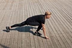 Mann, der das Bein tut Sport ausdehnt Stockbild