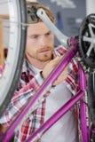 Mann, der das Fahrrad kontrolliert stockfotografie