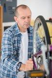 Mann, der das Fahrrad repariert stockbilder