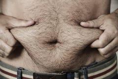 Mann, der das Fett seines Magens ergreift stockfotos