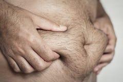 Mann, der das Fett seines Magens ergreift lizenzfreies stockfoto