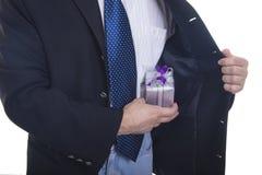 Mann, der das Geschenk versteckt unter seinem Mantel zeigt Stockbilder