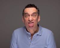 Mann, der das Gesicht heraus haftet Zunge zieht stockfotografie