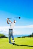 Mann, der das Golf, Ball vom T-Stück schlagend spielt lizenzfreie stockbilder