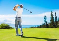 Mann, der das Golf, Ball vom T-Stück schlagend spielt Lizenzfreie Stockfotos