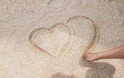 Mann, der das Herz auf goldenen Sand schreibt Lizenzfreies Stockfoto