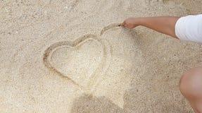 Mann, der das Herz auf goldenen Sand schreibt Stockfotografie
