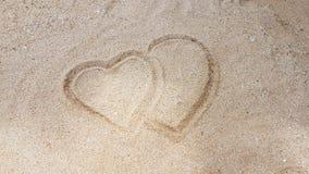 Mann, der das Herz auf goldenen Sand schreibt Lizenzfreie Stockfotos