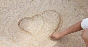 Mann, der das Herz auf goldenen Sand schreibt Stockbilder