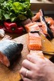 Mann, der das Mittagessen mit frischen Lachsfischen vorbereitet Stockfotos