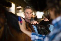 Mann, der das Pferd im Stall pflegt lizenzfreie stockfotografie