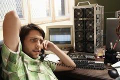 Mann, der das Telefon umgeben durch Computerausrüstung verwendet Lizenzfreies Stockbild