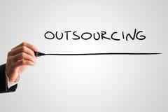 Mann, der das Wort Outsourcing schreibt Lizenzfreie Stockbilder