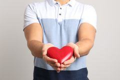 Mann, der dekoratives Herz auf hellem Hintergrund hält lizenzfreies stockbild
