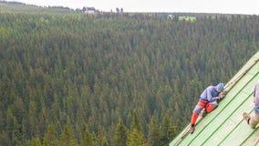 Mann, der an dem Dach, die Farbe reibend arbeitet Lizenzfreie Stockbilder