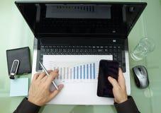 Mann, der an dem Laptop und dem Handy arbeitet Lizenzfreies Stockfoto
