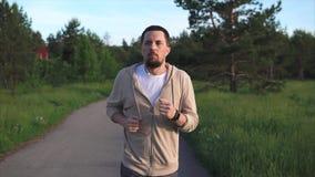 Mann, der an dem Sportlaufen teilnimmt, bereitet sich für einen Sprint im Parkbereich vor stock video