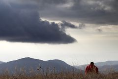 Mann, der an den Bergen stillsteht Lizenzfreie Stockfotografie
