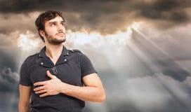 Mann, der den bewölkten Himmel schaut Stockfoto