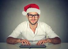 Mann, der den Computer kauft nach einem verwendet Weihnachtsgeschenk online, suchend lizenzfreies stockfoto