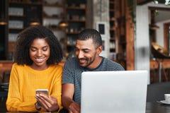 Mann, der den Handy seiner Freundin im Café betrachtet lizenzfreie stockbilder