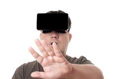 Mann, der den Kopfhörer VR-virtueller Realität heraus erreicht trägt Stockfoto