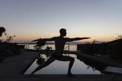 Mann, der den Krieger silhouettiert durch Pool tut Lizenzfreie Stockfotografie