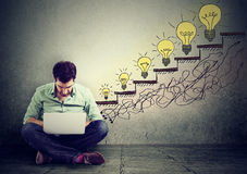 Mann, der den Laptop heranwächst Glühlampen als Symbol des Erfolgs verwendet Lizenzfreies Stockfoto