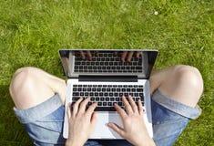 Mann, der den Laptop sitzt auf Gras verwendet Lizenzfreie Stockfotos