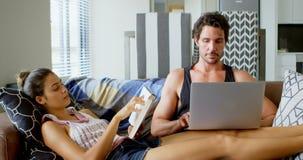 Mann, der den Laptop und Frau lesen ein Buch im Wohnzimmer 4k verwendet stock video