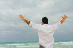 Mann, der den Ozean gegenüberstellt Stockfotografie