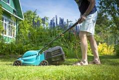 Mann, der den Rasen im Yard mäht Lizenzfreie Stockfotografie