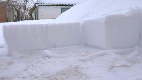 Mann, der den Schnee vom Weg schaufelt Schnee mit Schnee entfernend, schaufeln Sie vom Bürgersteig nach Schneesturm Schneewürfel stock footage