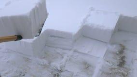 Mann, der den Schnee vom Weg schaufelt Schnee mit Schnee entfernend, schaufeln Sie vom Bürgersteig nach Schneesturm Schneewürfel stock video footage