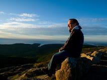Mann, der den Sonnenaufgang über dem Meer aufpasst Stockfotografie