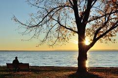 Mann, der den Sonnenaufgang über einem See Ende des Falles aufpasst Lizenzfreie Stockfotografie