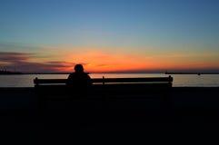 Mann, der den Sonnenuntergang aufpasst Lizenzfreie Stockfotografie
