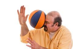 Mann, der den Sport geschlagen wird durch einen Korbball spielt Stockbild