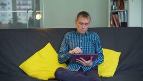 Mann, der den Tablet-PC in seinem Appartement verwendet stock video