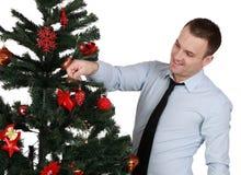 Mann, der den Weihnachtsbaum verziert Stockbild