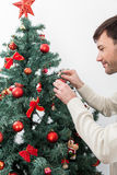 Mann, der den Weihnachtsbaum verziert Lizenzfreies Stockbild