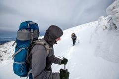 Mann, der in den Winterbergen vor Gewitter wandert Lizenzfreie Stockfotografie