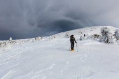 Mann, der in den Winterbergen vor Gewitter wandert Lizenzfreie Stockbilder