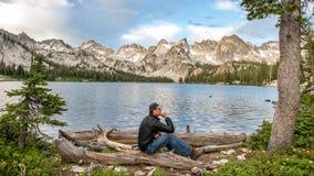 Mann in der Denkungsposition an einem Gebirgssee lizenzfreies stockfoto