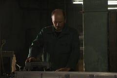 Mann, der in der dunklen Fabrik arbeitet stockfotos