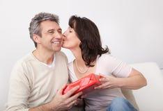 Mann, der der Frau ein Geschenk gibt Stockbilder